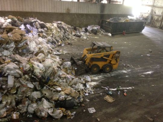 A WastAway employee operating a small bulldozer scoops up trash dumped into the warehouse in Morrison before transferring the waste to the area where the metals are separated for recycling. (Photo: Scott Broden/DNJ)